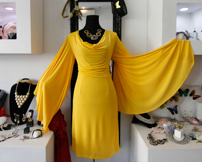 Vestido amarillo de punto de seda Cocoa con mangas de vuelo y collar negro y dorado de piedras y croché