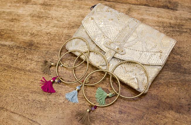 Bolso de mano en piel print animal y pulseras doradas con pompones de colores