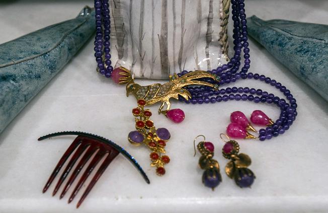 Collar de perlas con figura de ave y pendientes bañados en oro y creados con piedras de colores, y peina con detalle brillante