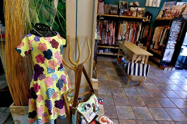 En primer plano, vestido estampado floral y carteras y bolsos de la marca inglesa Disaster Desings