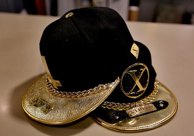 Gorras con acabado charol dorado y combinado en piel de serpiente, cadena de eslabón ancho y emblema metálico bañado en oro de Xtress