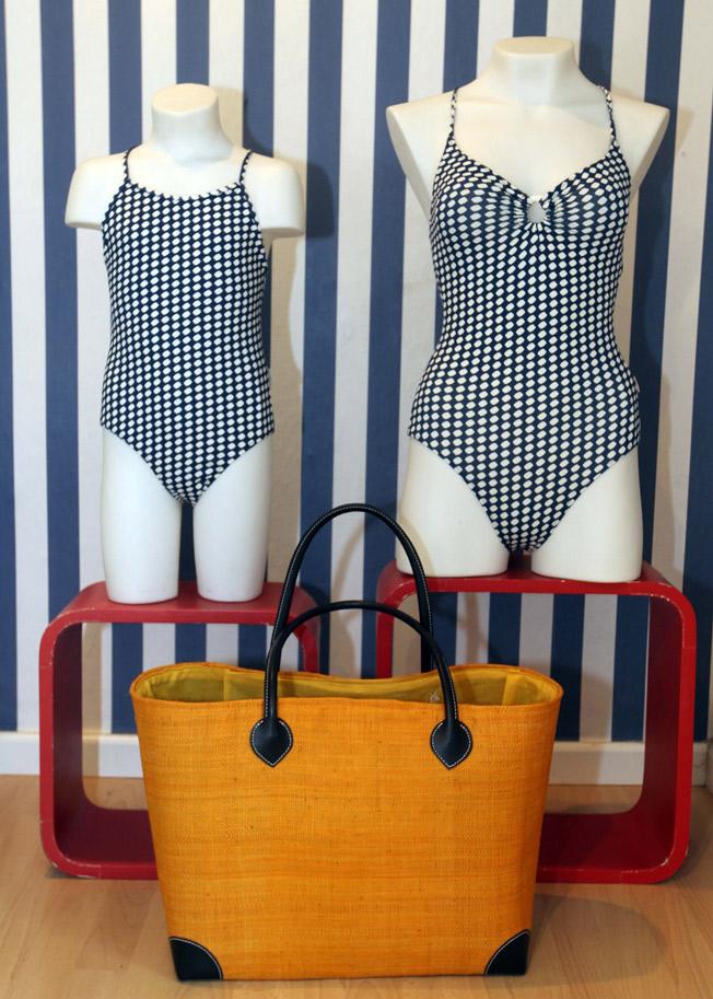 Bañadores de mujer y niña con estampado geométrico sobre fondo azul marino y bolso con doble asa corta de piel