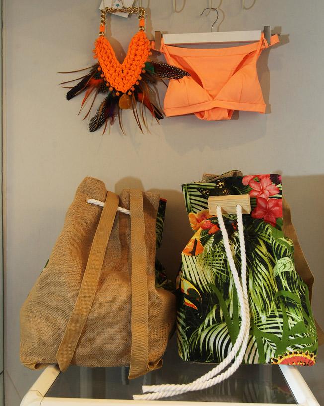 Mochilas saco estampado tropical, biquini sporty salmón y collar trapillo naranja con piedras y plumas