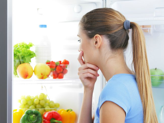 Young woman craving food choosing near refrigerator