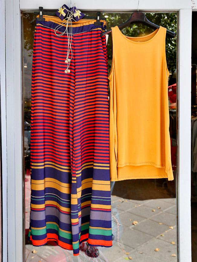 Pantalón campana estampado de rayas multicolor, camiseta de lycra mostaza sin manga y cinturón de Denebola