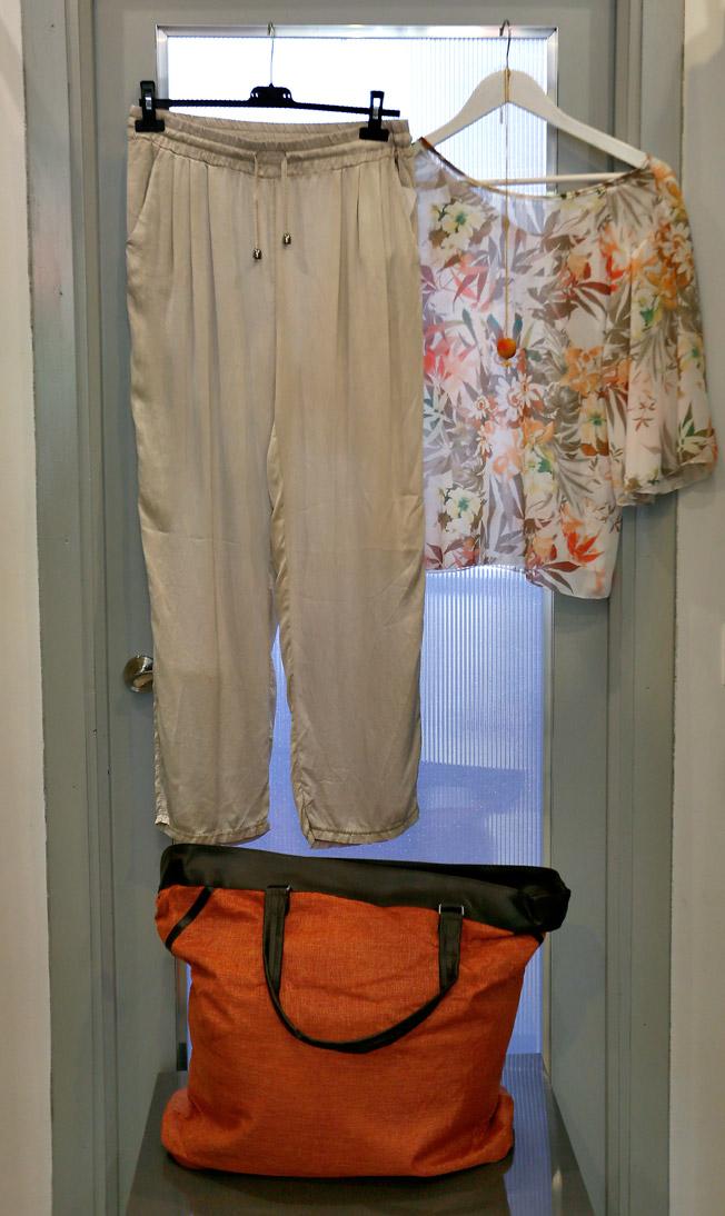 Pantalón de seda recto beige con bolsillos, camisa de gasa estampado floral, colgante y bolso color teja en tela y piel