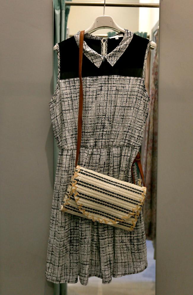 Vestido blanco y negro en gasa con corte a la cintura y cuello camisero, y bolso bandolera en rafia bicolor