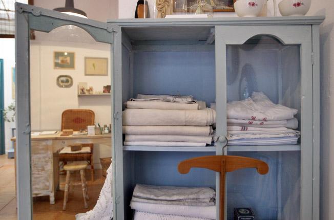 En la vitrina, antiguos manteles, sábanas y camisones de lino y mantas blancas de crochet