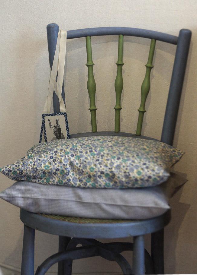 Silla antigua con asiento de rejilla y cojines en tonos azules y verdes con telas liberty y vichy