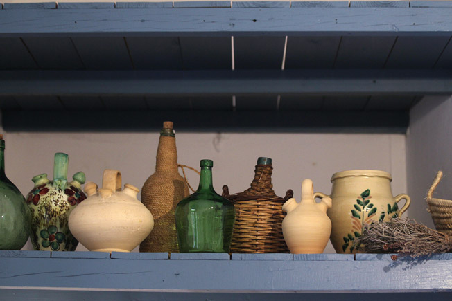 Altillo de madera con colección de piezas populares españolas, como tinajas, botijos y garrafas