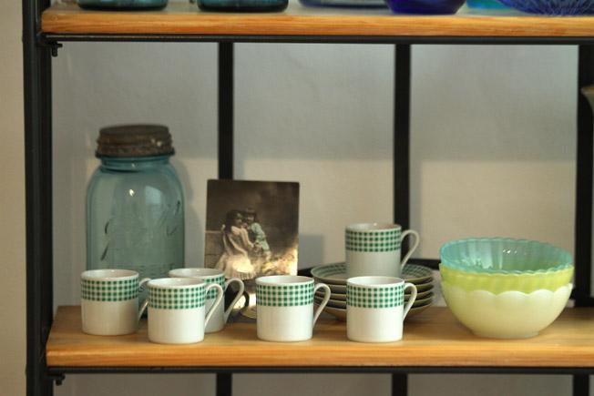 Juego de café vintage de porcelana con cuadros de Vichy en verde y blanco, junto a boles de cristal en colores pastel de la marca francesa Dulcine