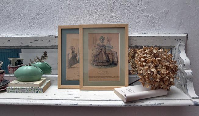 Perchero modernista reciclado y convertido en aparador, con antiguas portadas de revistas de moda francesas del siglo XIX enmarcadas