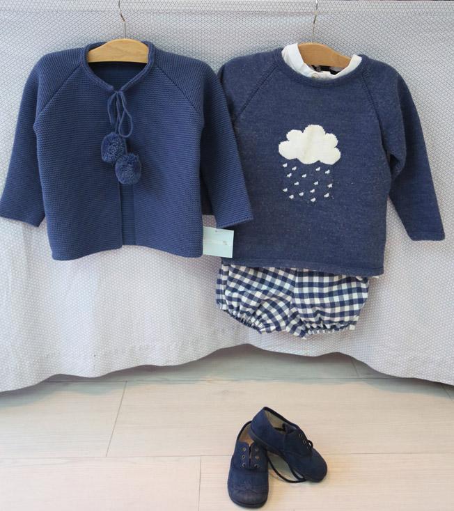 Rebeca con pompones y jersey azulón con nube blanca, bermudas de cuadros en tonos azul y blanco, y zapatos a juego