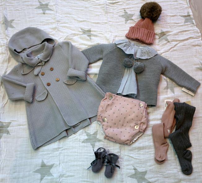 Conjunto de cubrepañal rosa con estrellas en gris, rebeca con pompones gris, gorro rosa con pompón de pelo y abrigo gris, con leotardos y patucos a juego