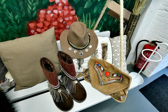 Botas cosidas a mano con flecos y monedas, sombrero con detalle de monedas y cuero, y cartera de mano en piel de ante con piedras de colores e incrustaciones metálicas, artesanía de la firma Tarifa Soul