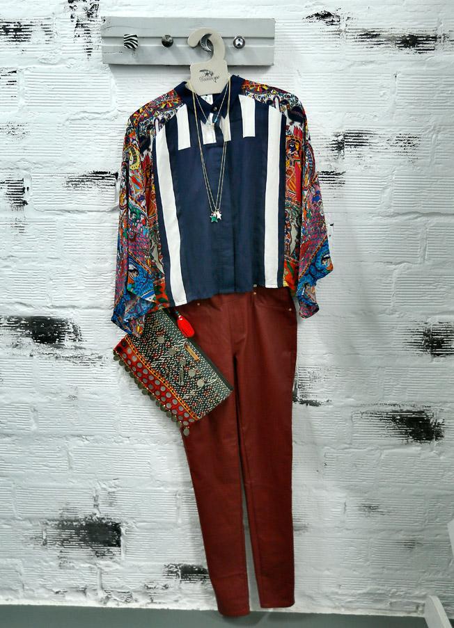 Camisa de seda exclusiva estampada en la India, carteras de mano cosidas con piedras y monedas antiguas, realizadas por Clara Baconce, junto a pantalón pitillo burdeos