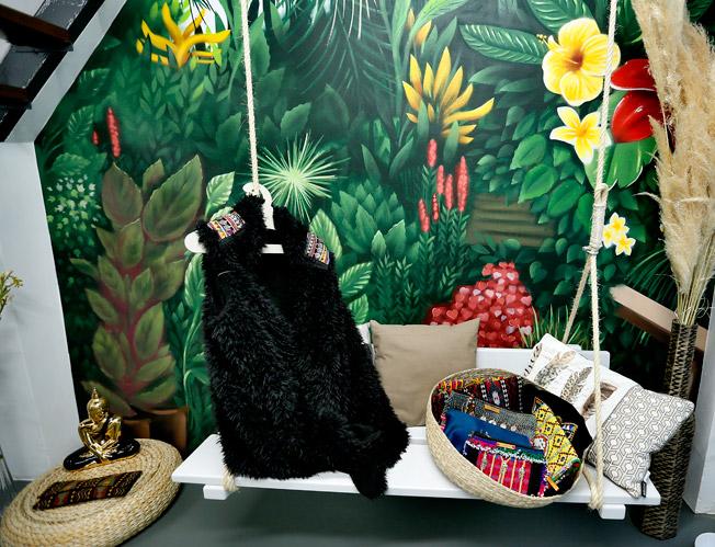 Chaleco de borrego negro con detalle en los hombros de monedas y telas cosidas en diferentes colores, junto a bolsos y carteras cosidos con piedras y monedas, realizados por Clara Baconce