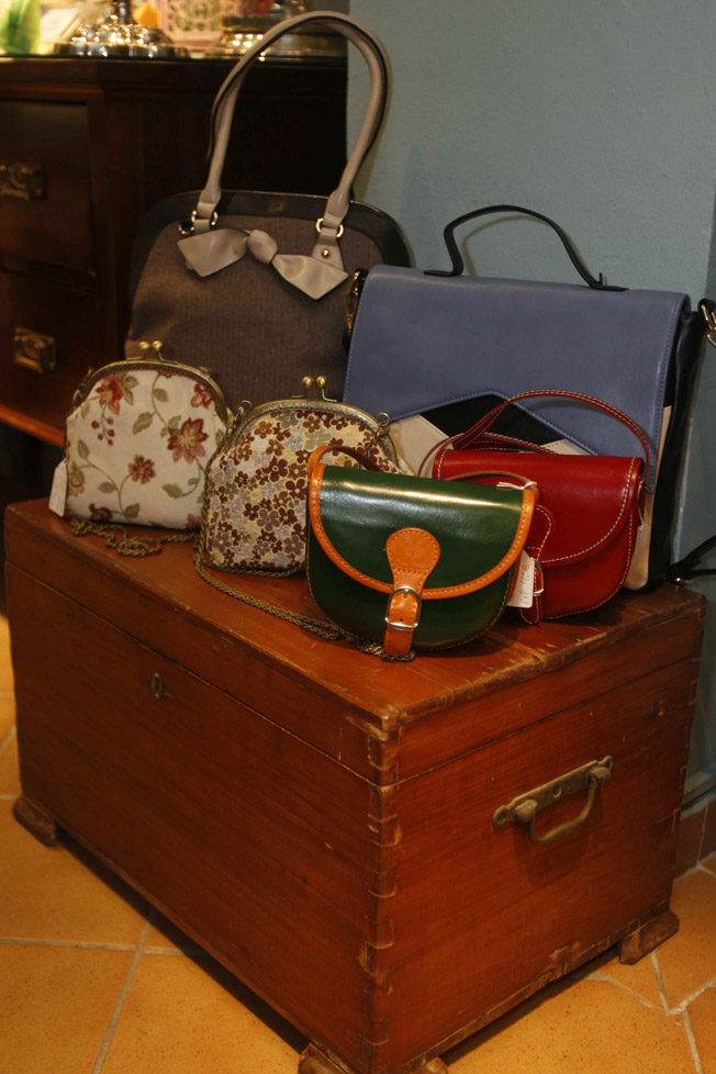 Baúl antiguo con compartimento secreto de época, con bolsos de diferentes estampados y estilo vintage