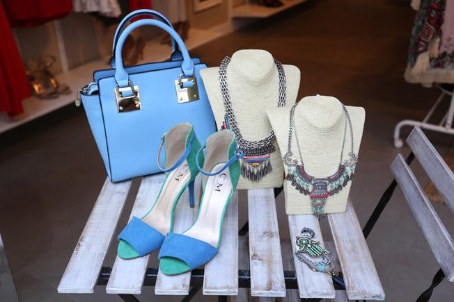 Collares étnicos junto a bolso en tono pastel celeste y sandalias bicolor