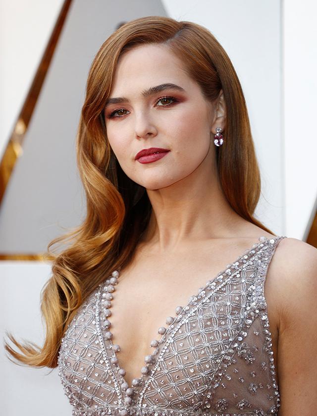 Zoey Deutch apostó por unas ondas Hollywood para lucir su bonita melena pelirroja y por un maquillaje «total look» en tonos burdeos. (EFE)