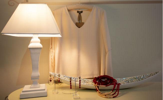 Camisa beige, bandeja decoración y pendientes en tonos frambuesa